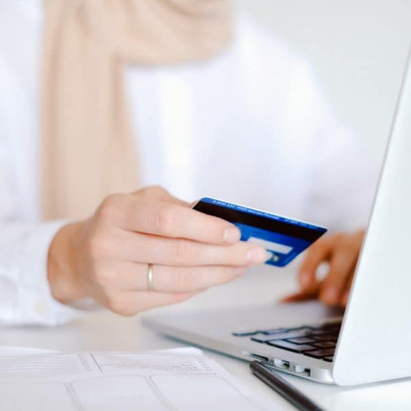 Person in long sleeve white shirt holding credit card