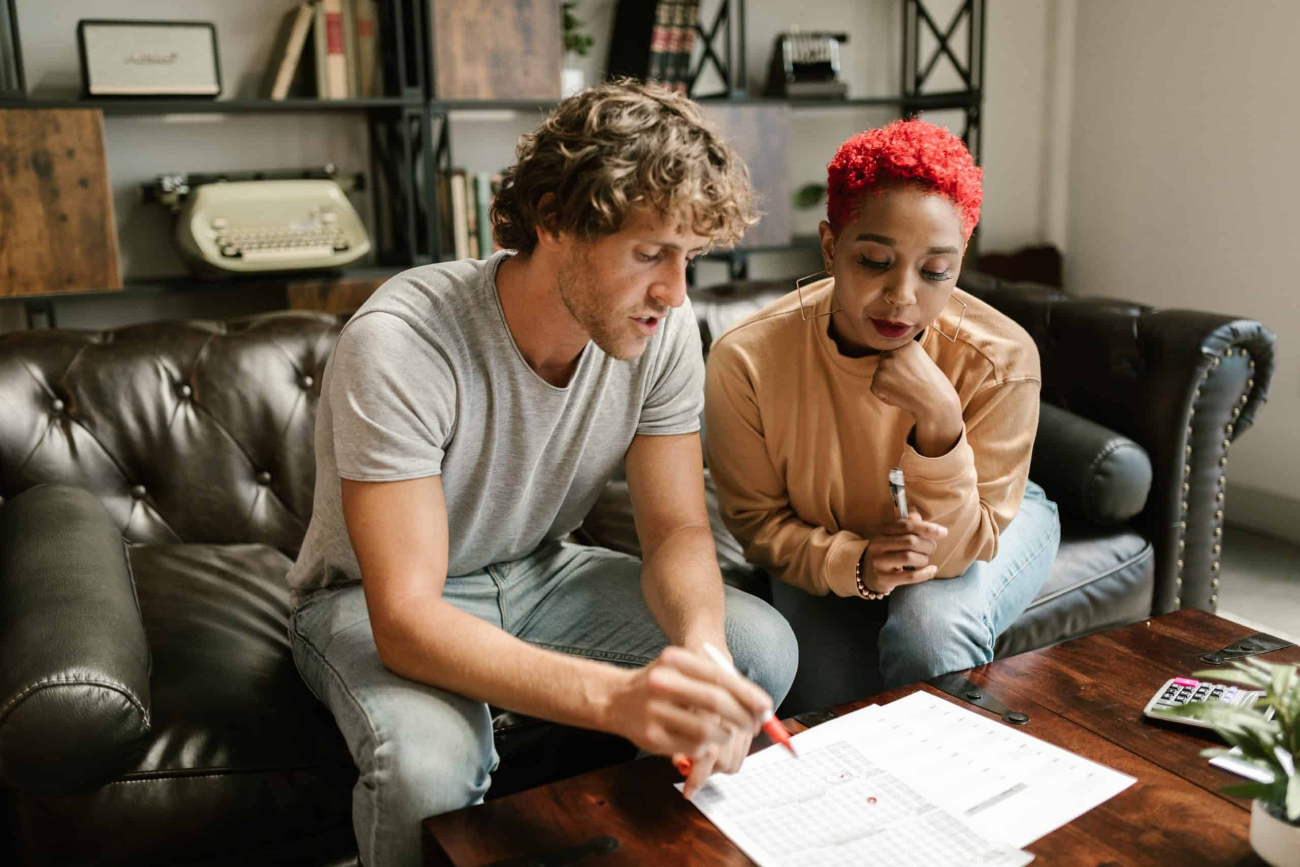 White man and black woman look closely at financial documents